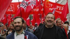Opposition activists Gennady Gudkov, right, and Ilya Ponomarev, a lawmaker, left, march with opposition supporters heading to a protest rally in Moscow, September 15, 2012.