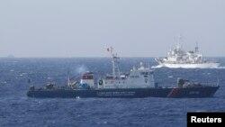 中國海警船(上)和越南海岸警衛隊船隻(下)5月14日在離越南210公里海域附近對峙。