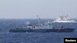지난달 14일 남중국해 영유권 분쟁 해역에서 중국 해안감시선(위)과 베트남 해경선(아래)이 대치하고 있다. (자료사진)