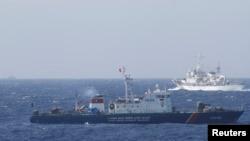 Kapal penjaga pantai China (atas) dan kapal AL Vietnam berpapasan di perairan sengketa di Laut China selatan (14/5). Kedua negara membawa sengketa wilayah kepada Sekjen PBB.
