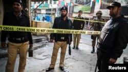Para petugas keamanan menyegel lokasi pemboman bunuh diri di Rawalpindi, Pakistan (20/1).