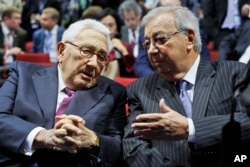 FILE - Former Russian premier minister Yevgeny Primakov, right, and former U.S. Secretary of State Henry Kissinger speak as they take part in economic forum in St.Petersburg, Russia, June 21, 2012.