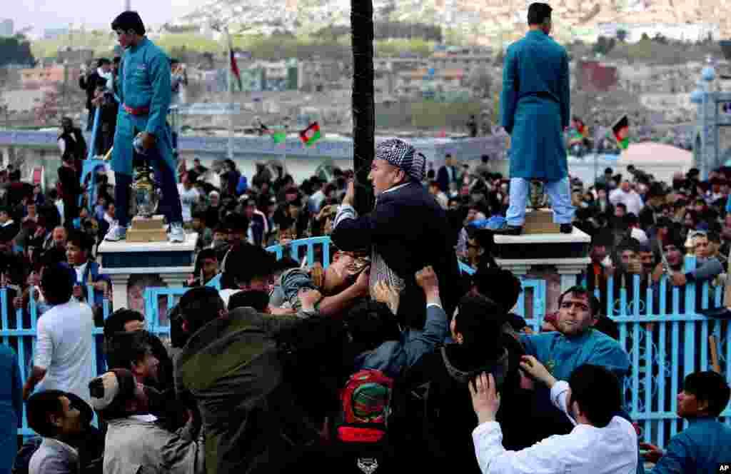 در حاشیه مراسم سال نو، یک مرد افغان در زیارتگاه کارته سخی یک علم را می بوسد. افغانها، این زیارتگاه را قدمگاه حضرت مولا علی می دانند.