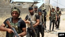 FILE - Fighters from the Popular Mobilization units deploy in the city of Baiji, north of Tikrit, as they fight alongside Iraqi forces against the Islamic State, June 9, 2015.