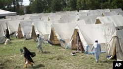 Displaced Pakistanis living a tent camp set up by the army on the outskirts of Nowshera, Pakistan, 2 Aug 2010.