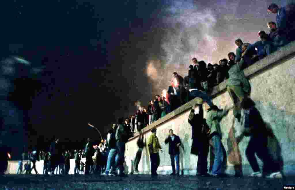 مشرقی جرمنی کی سرحد پر واقع برانڈنبرگ گیٹ پر لوگ دیوار برلن پر چڑھے ہوئے ہیں۔ دیوار کے انہدام کے لیے مشرقی جرمنی کے باسی اکثر احتجاج کرتے تھے۔ جس کے نتیجے میں انقلاب آیا۔ 9 نومبر کو دیوار برلن مسمار ہوئی اور اس کے اگلے سال جرمن اتحاد وجود میں آیا۔