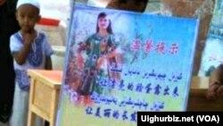 喀什街头的一个维吾尔男孩站在一幅宣传画后面。地方当局将维族妇女带面纱头巾归 为陋俗。(图片来源:维吾尔在线)