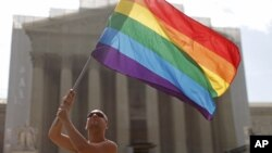 Vin Testa from Washington, waves the rainbow flag in support of gay marriage in front of the Supreme Court in Washington, Monday, June 24, 2013. The Supreme Court has 11 cases, including the term's highest profile matters, to resolve before the justices t