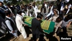 FILE - Afghans take part in a burial ceremony of Afghan journalist Zabihullah Tamanna, in Kabul, Afghanistan, June 7, 2016.