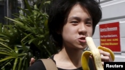 FILE - Amos Yee eats a banana as he arrives to the State Courts for a pre-trial conference in Singapore, April 17, 2015.