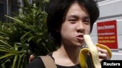 Amos Yee makan pisang saat tiba di pengadilan Singapura untuk konferensi pra-peradilan (17/4). (Reuters/Edgar Su)