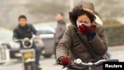 Seorang perempuan mengenderai sepeda sambil mengenakan masker di tengah asap kabut di Beijing, China (foto: dok).