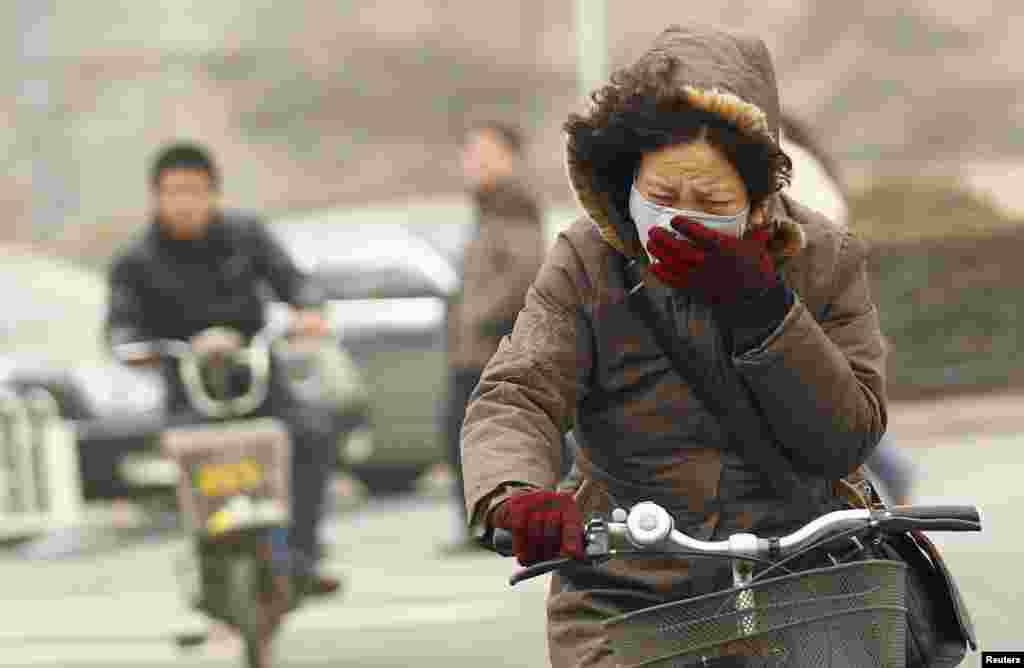 中國北京,一位女士戴著口罩騎自行車穿過濃厚的晨霧。