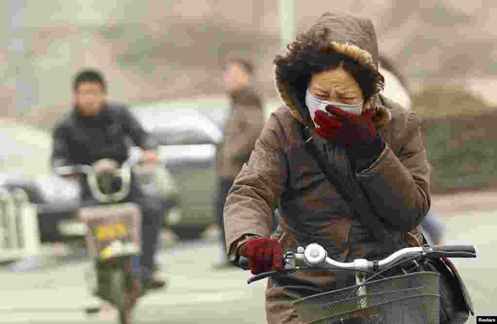 Trời mù sương khói vào buổi sáng tại Bắc Kinh, Trung Quốc buộc nhiều người phải mang khẩu trang.