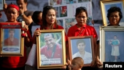 Anti-government ''red shirt'' protesters hold pictures of killed friends, relatives and late Italian photographer Fabio Polenghi, Bangkok's, May 19, 2011.