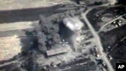 In this photo made from the footage taken from Russian Defense Ministry official web site on Oct. 4, 2015, an aerial view of a bomb explosion in Syria.