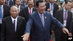 Cambodia's Prime Minister and President of the People's Party, Hun Sen, center, arrives at an event marking the 38th anniversary of the 1979 downfall of the Khmer Rouge regime in Phnom Penh, Cambodia, Saturday, Jan. 7, 2017. (AP Photo/Heng Sinith)
