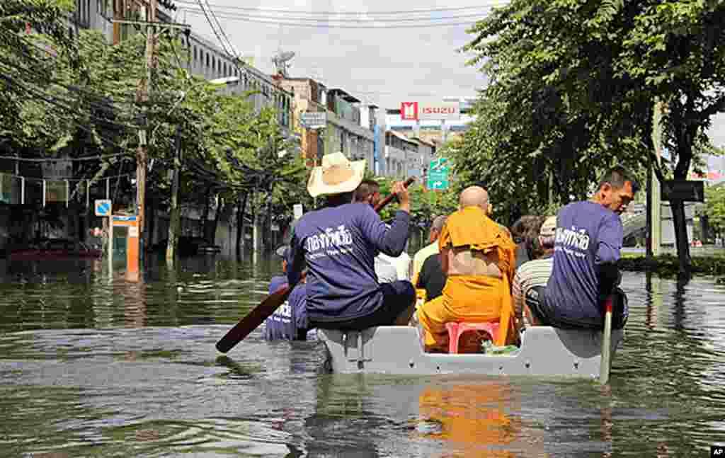 海军小舟载着一名僧人和其他居民驶过街区
