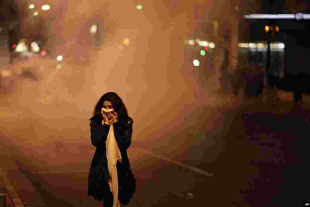 A pedestrian covers her face to protect from tear gas during a protest in front of the Greek parliament in Athens. (AP)