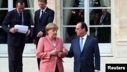 Kanselir Jerman Angela Merkel berbicara dengan Presiden Perancis Francois Hollande di Paris di sela KTT Balkan 4 Juli 2016 lalu (foto: dok).
