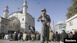 Seorang polisi Afghanistan berjaga saat warga menunaikan ibadah sholat Idul Adha di luar mesjid Shah-e-Dushamshera di Kabul, Afghanistan (26/10).