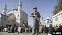 ເຈົ້າໜ້າທີ່ຕໍາຫລວດຄົນນຶ່ງ ກໍາລັງຢືນຍາມຝູງຄົນ ທີ່ພາກັນ ສູດມົນ ມື້ບຸນ Eid al-Adha ທີ່ວັດແຫ່ງນຶ່ງ ໃນເມືອງຫລວງ Kabul, ອັຟການິສຖານ