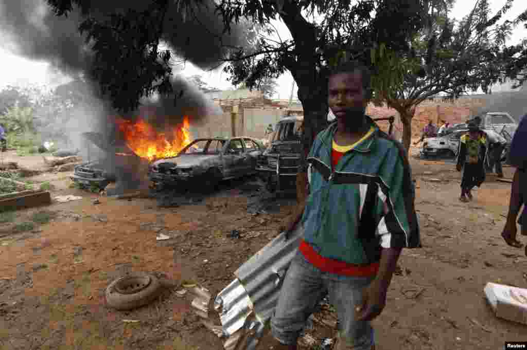 A man takes part in looting a mosque in Fouh district in Bangui, Central African Republic, Dec. 10, 2013.