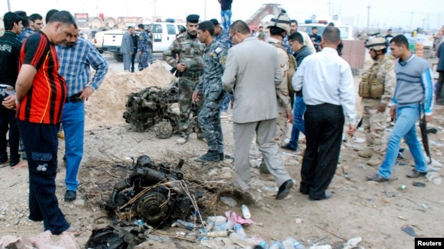 Iraqi security forces inspect site of car bomb attack in Kut, 150 km (93 miles) southeast of Baghdad, Nov. 28, 2013.