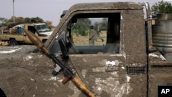 A rocket propelled launcher hangs on the mirror of a pickup truck in the Nigerian city of Damasak March 18, 2015.