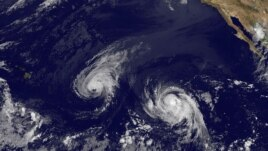 This image provided by NOAA Aug. 6, 2014 shows Hurricane Iselle, center, and tropical storm Julio, right.