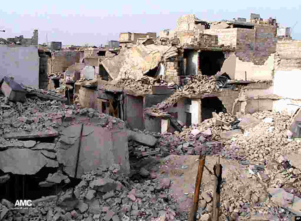 This citizen journalism image provided AMC shows homes destroyed by Syrian government airstrikes and shelling in Karam Tarab near Aleppo International Airport, Syria, July 2, 2013.