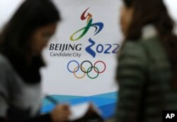 Para jurnalis mengobrol di dekat logo Olimpiade Musim Dingin 2022 di Markas Besar Olimpiade Beijing di Beijing, China, 4 November 2014.