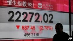 Un homme passe devant un écran de l'indice Hang Seng devant une banque à Hong Kong, le 9 novembre 2016.