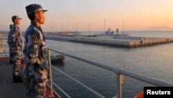 Dua tentara Angkatan Laut China siaga mengawasi kawasan sengketa di Laut China Timur yang diklaim Beijing sebagai zona pertahanan udaranya (2/12).