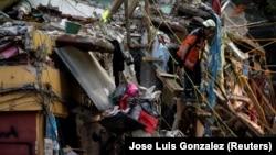 Seorang anggota tim penyelamat Argentina berjalan menuruni tangga dengan anjing pelacaknya, di lokasi perumahan multi-keluarga yang runtuh, setelah gempa bumi, di Mexico City, Meksiko 24 September 2017. (Foto: REUTERS/Jose Luis Gonzalez)