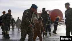 FILE - An Afghan National Army officer escorts a slightly injured boy from the site of a suicide attack on the outskirts of Mazar-e-Sharif, Afghanistan, Feb. 8, 2016.