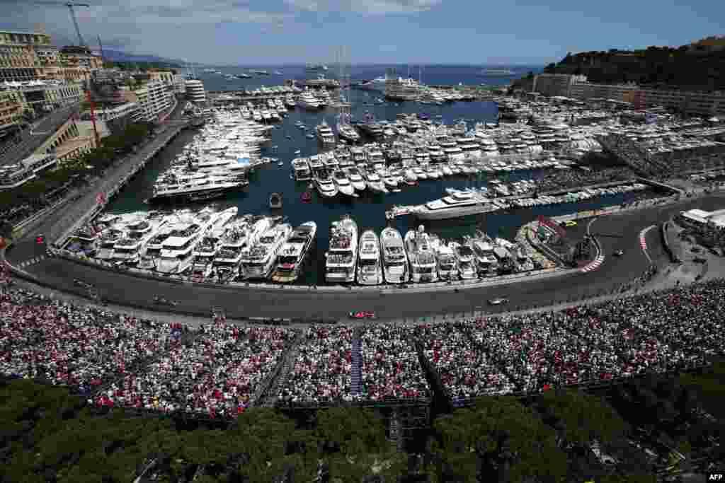 អ្នកទស្សនាមើលការប្រកួតឡានប្រណាំងនៅតាមបណ្តោយកំពង់ផែ នៅក្នុងកម្មវិធី Monaco Formula One Grand Prix ក្នុងតំបន់ Monte-Carlo ប្រទេសម៉ូណាកូ (Monaco) ។