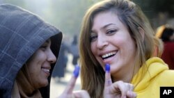 Dua perempuan Mesir menunjukkan jari bertinta penanda telah memberikan suara dalam referendum mengenai rancangan konstitusi baru (15/12). (AP/Amr Nabil)