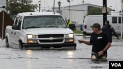 Seorang laki-laki memberi petunjuk jalan bagi pengendara truk melintasi banjir akibat badai tropis Lee di New Orleans (3/9).