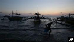 ငါးဖမ္းစက္ေလွမွာ အသံုးျပဳမယ့္ သိုေလွာင္ခန္းအသစ္တခု ေရခ် သယ္ေဆာင္လာေနတဲ့ ဖိလစ္ပိုင္လူငယ္တစ္ဦး။