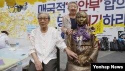 지난 14일 서울 주재 일본대사관 앞에서 열린 '세계 일본군 위안부 기림일' 행사에 참석한 위안부 동원 피해자 김복동 할머니가 소녀상 옆에 앉아있다. 오른쪽은 길원옥 할머니.