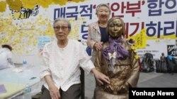 지난 2016년 8월 오후 서울 종로구 중학동 주한 일본대사관 앞에서 '세계 일본군 위안부 기림일'을 맞아 열린 '나비 문화제'에 참석한 김복동 할머니가 소녀상 옆 빈 의자에 앉아있다. 오른쪽은 길원옥 할머니.