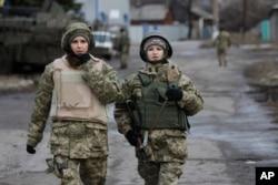 FILE - Ukrainian government army women soldiers patrol an area in the village of Debaltseve, Donetsk region, eastern Ukraine, Dec 24, 2014.