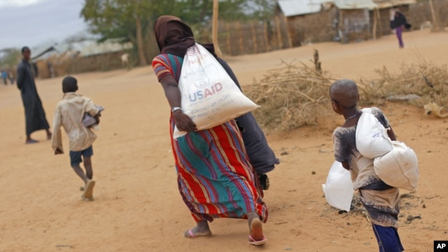 A newly-arrived Somali family carry their supply of aid outside Dadaab, Eastern Kenya, 100 kms (60 miles) from the Somali border, Aug. 5, 2011