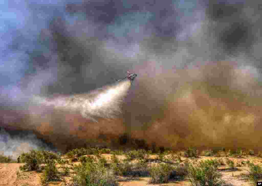This photo provided by the San Bernardino County Fire Department shows a helicopter making a drop on a wildfire that started in western Arizona and jumped the Colorado River into California, near Needles, California, April 6, 2016.