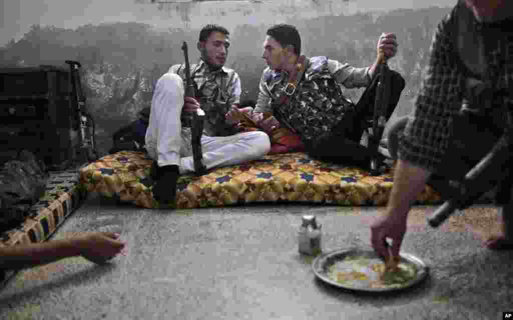 A Syrian rebel fighter, right, eats while others chat as they wait for transportation to go fight government forces in Aleppo, September 10, 2012.