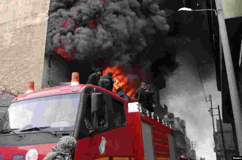 Firefighters attempt to extinguish a fire at a factory after what activists say was shelled by forces loyal to Syria's President Bashar al-Assad at al-Haidariah area in Aleppo.