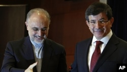Turkish Foreign Minister Ahmet Davutoglu, right, and his Iranian counterpart Ali Akbar Salehi leave after a news conference in Ankara, Turkey, October 21, 2011.