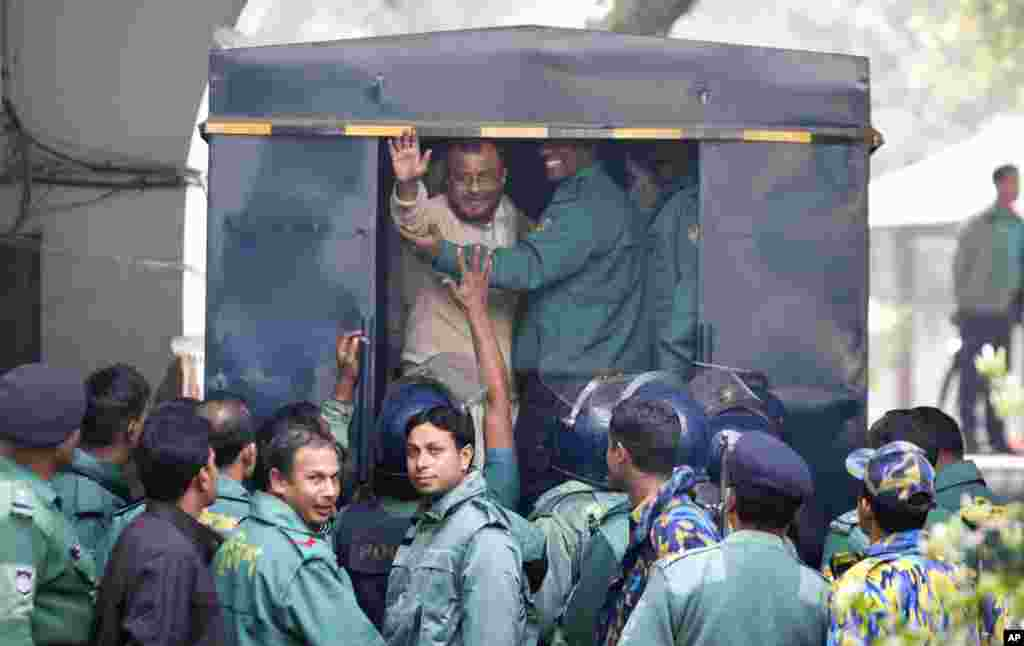 A.T.M. Azharul Islam, assistant secretary general of the Jamaat-e-Islami party, waves his hand as he enters a police van after a special tribunal sentenced him to death in Dhaka, Bangladesh.