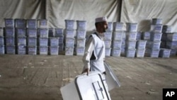 An Afghan election worker carries ballot boxes at the warehouse of Afghanistan's Independent Election Commission in Kabul, Afghanistan, a few days after parliamentary elections on September 18, 2010.